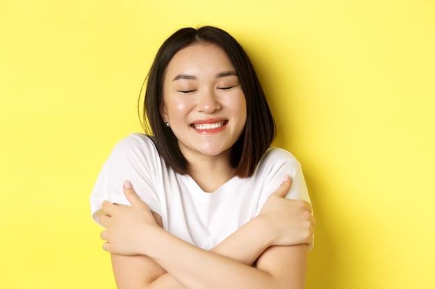 Primo piano di una romantica ragazza asiatica che si abbraccia e sogna, chiudi gli occhi e sorridi mentre immagini qualcosa di tenero, in piedi su sfondo giallo
