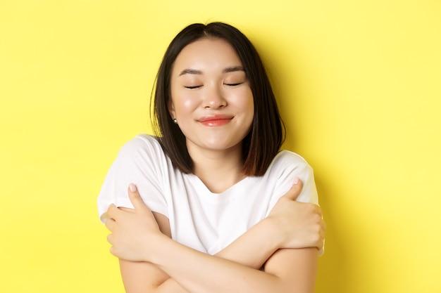 Primo piano di una romantica ragazza asiatica che si abbraccia e sogna, chiudi gli occhi e sorridi mentre immagini qualcosa di tenero, in piedi su sfondo giallo.