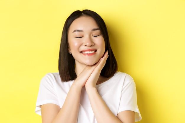 Primo piano di una romantica donna asiatica che sogna qualcosa di carino, chiudi gli occhi e tieni le mani vicino al viso, immaginando cose belle, in piedi su sfondo giallo.