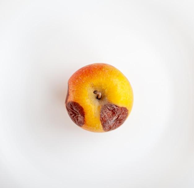 Primo piano di una mela marcia isolata su uno sfondo bianco con uno spazio di copia.