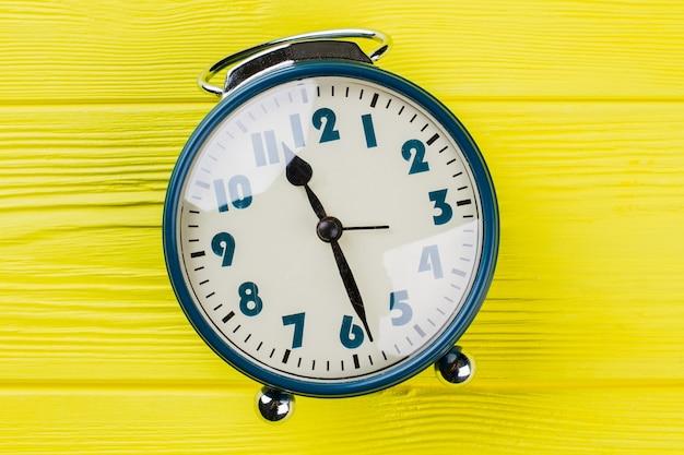 Close up orologio rotondo con vetro riflettente. la lancetta dell'orologio mostra le undici e mezza. fondo di legno giallo.