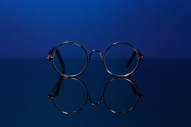 Close-up di bicchieri rotondi con la riflessione dal tavolo di vetro.