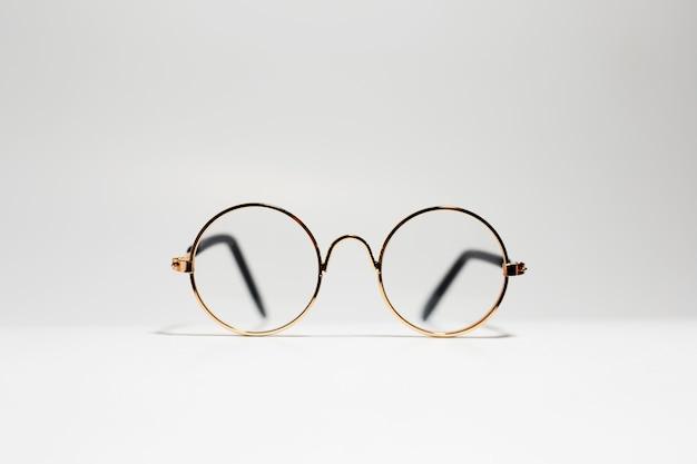 Primo piano degli occhiali rotondi dell'oro isolati su bianco