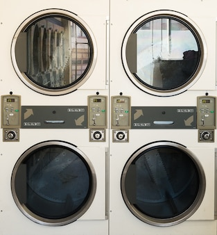 Chiuda sulla fila della lavatrice dell'affare della lavanderia nel deposito pubblico.