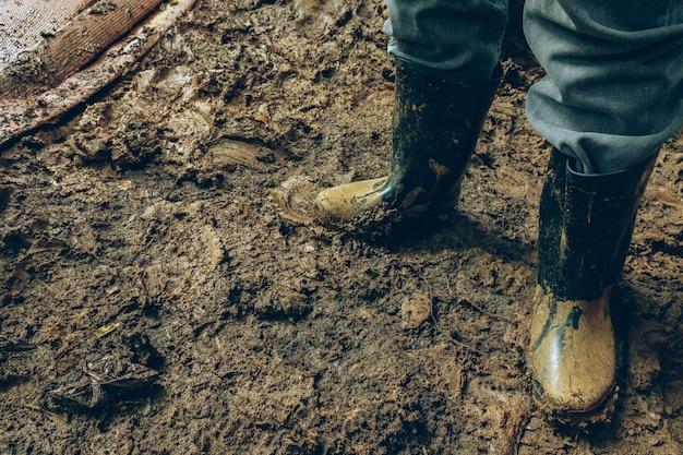 Chiuda sullo stivale di gomma della pioggia con il lavoro del fango o il posto sporco.