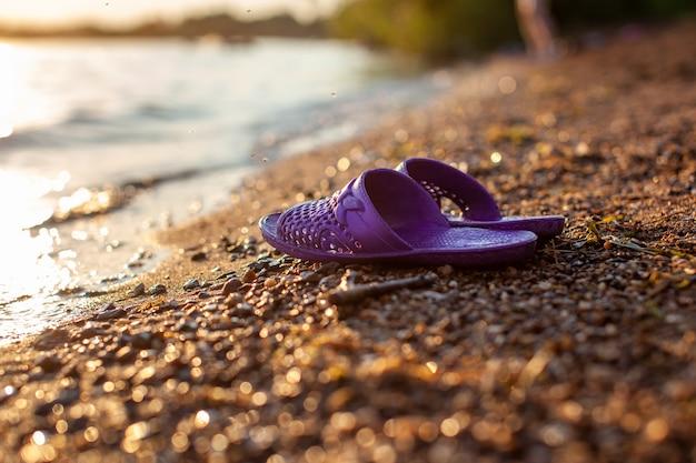 Primo piano di pantofole di gomma sulla riva di un lago o di un fiume fatto di piccole pietre contro uno sfondo colorato del tramonto. un bel posto nella natura per le vacanze in famiglia e il nuoto.