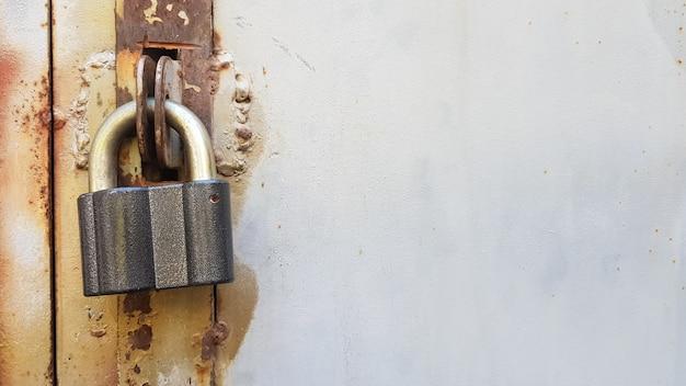 Primo piano di una porta di metallo arrugginita con un lucchetto chiuso.