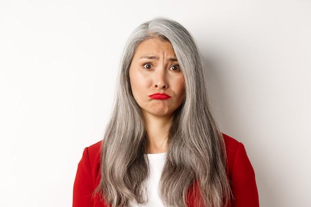 Primo piano di triste e infelice donna senior asiatica imbronciato, accigliato e guardando geloso alla telecamera, in piedi su sfondo bianco.
