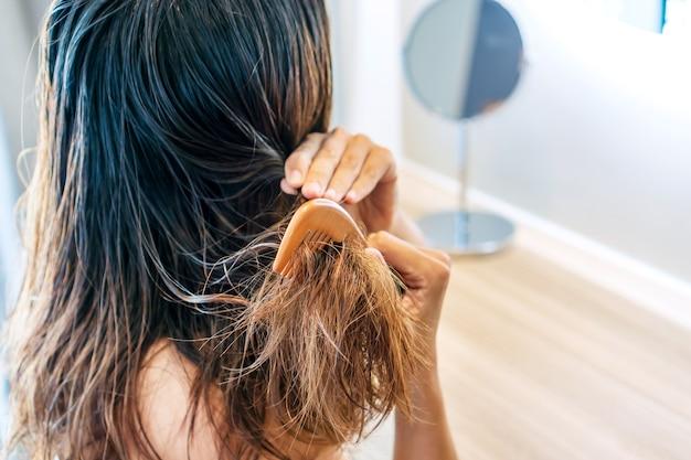 Chiuda in su della giovane donna asiatica triste spazzolare i capelli bagnati danneggiati e aggrovigliati