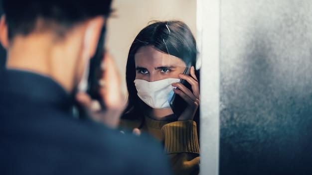 Avvicinamento. triste giovane coppia in maschere protettive che si guardano. foto con copia-spazio