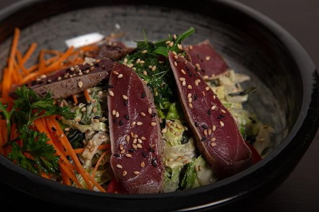 Primo piano della ciotola di insalata con tataki di tonno. cucina asiatica