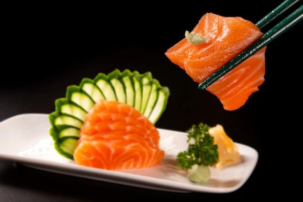 Chiuda sul sashimi di color salmone con i salmoni in un piatto bianco desfocused. su uno sfondo nero