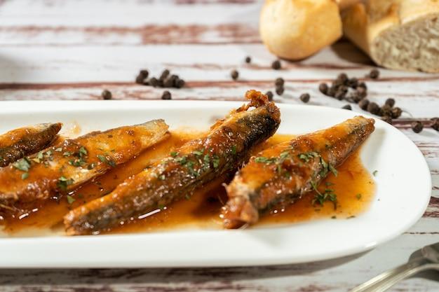 Close-up di sardine in salsa di pomodoro e prezzemolo servito in un piccolo piatto bianco. alta vista. copia testo.