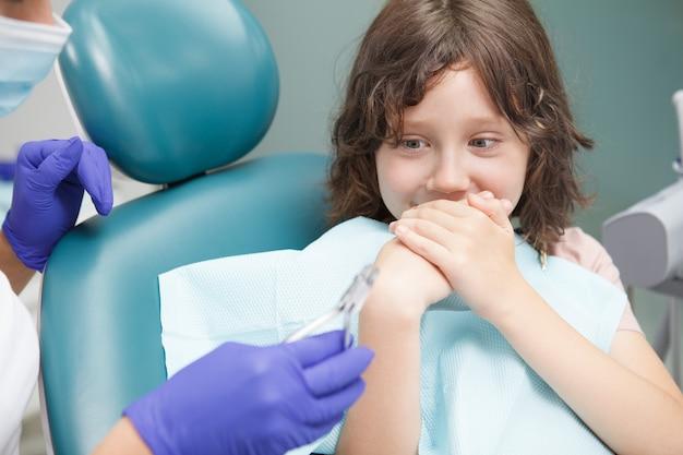 Primo piano di un ragazzo spaventato che si copre la bocca con le mani, impaurito dal trattamento dentale