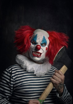 Primo piano di un spaventoso clown malvagio con capelli rossi, occhi bianchi, denti insanguinati, ascia in mano e uno sguardo minaccioso