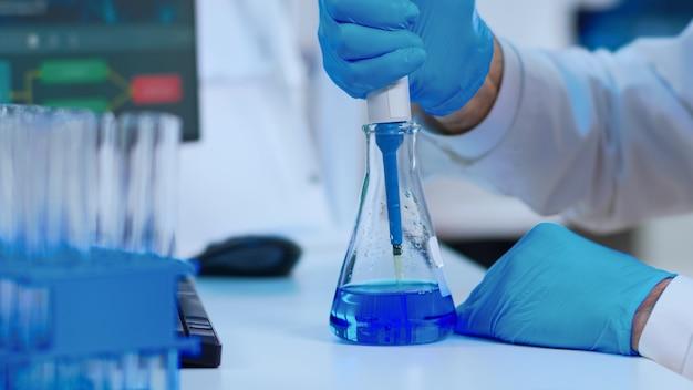 Primo piano dello scienziato che riempie la provetta con liquido utilizzando una pipetta in un laboratorio attrezzato. scienziato che analizza vari batteri, tessuti e campioni di sangue, ricerca farmaceutica per antibiotici