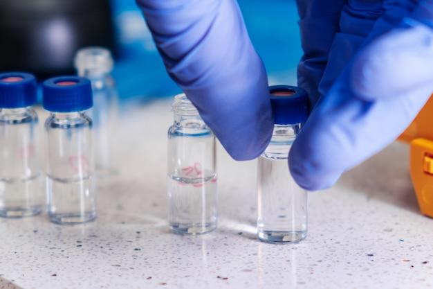 Close up scienziato mano in guanti di gomma prende una fiala di vetro con un tappo blu per l'analisi hplc