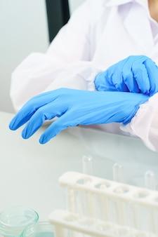 Close up scienziato mani mettendo in nitrile guanti di lattice blu in camice da laboratorio indossando guanti di nitrile, facendo esperimenti in laboratorio