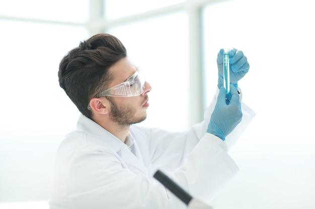 Avvicinamento. scienziato con un tubo medico in piedi in laboratorio. scienza e salute