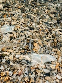 Vicino mare onde pietre conchiglie spiaggia giorno d'estate. vista dall'alto sopra l'acqua trasparente. oceano mare limpido