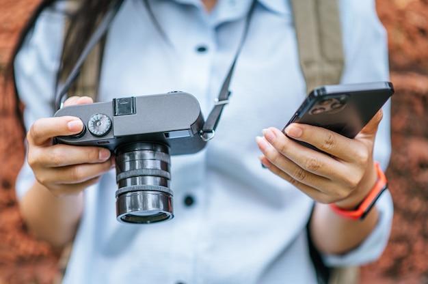 Primo piano e messa a fuoco selettiva mano femminile che tiene smartphone e fotocamera digitale durante il viaggio in un antico sito