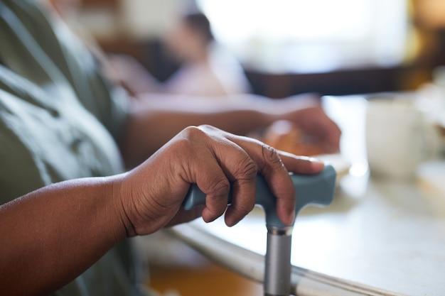 Primo piano di una donna afroamericana anziana che tiene la casa di cura della canna da zucchero e lo spazio della copia di sfondo della mobilità