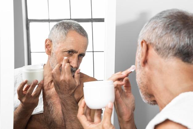 Uomo maggiore del primo piano che applica crema per il viso