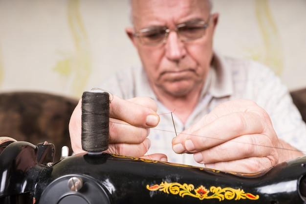 Primo piano di un uomo anziano in profonda concentrazione per infilare l'ago della vecchia macchina da cucire manuale