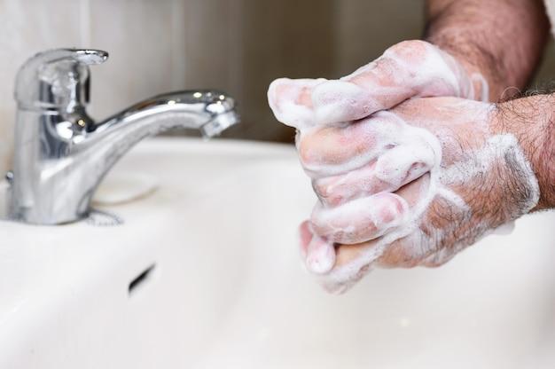 Primo piano di uomo anziano lavarsi le mani con schiuma di sapone, prevenzione da covid19, coronavirus o batteri. concetto di assistenza sanitaria