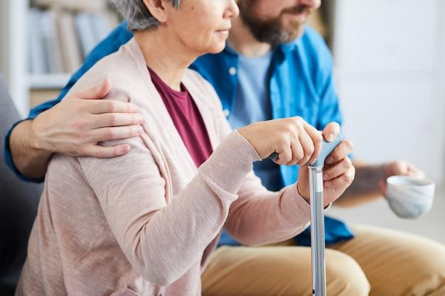 Primo piano della donna maggiore che tiene la stampella e che si siede sul divano con un infermiere che la abbraccia e che si siede nelle vicinanze