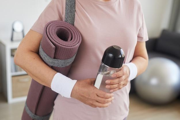 Primo piano della stuoia di esercitazione della tenuta della donna maggiore e una bottiglia d'acqua che è pronta per l'allenamento sportivo