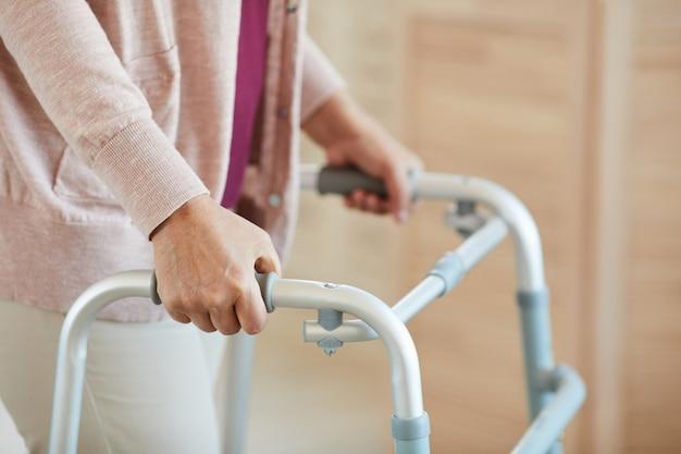 Primo piano della donna maggiore che si appoggia sul deambulatore e cammina lungo la stanza