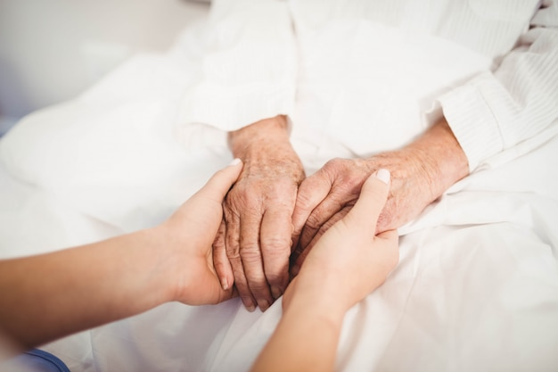Primo piano di tenersi per mano senior dell'infermiere e della donna