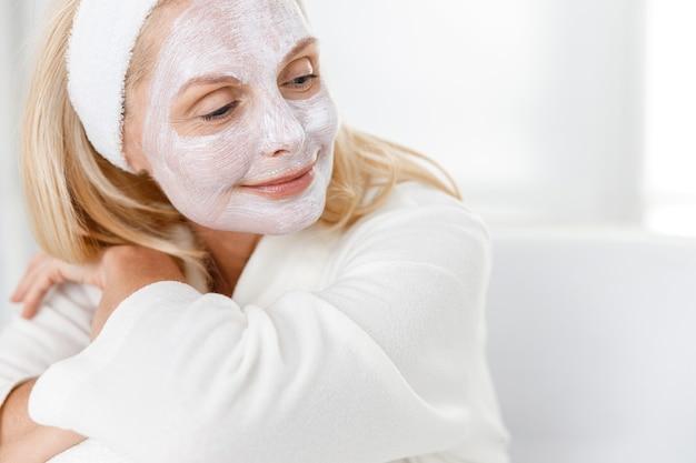Primo piano di donna senior con maschera di nutrizione sul viso, visitando i cosmetologi nel moderno centro medico.