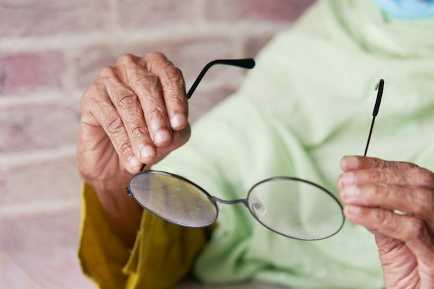 Primo piano di una donna anziana che tiene in mano un vecchio occhiale