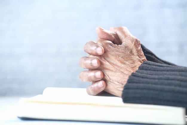 Chiuda in su della mano delle donne senior che prega a.