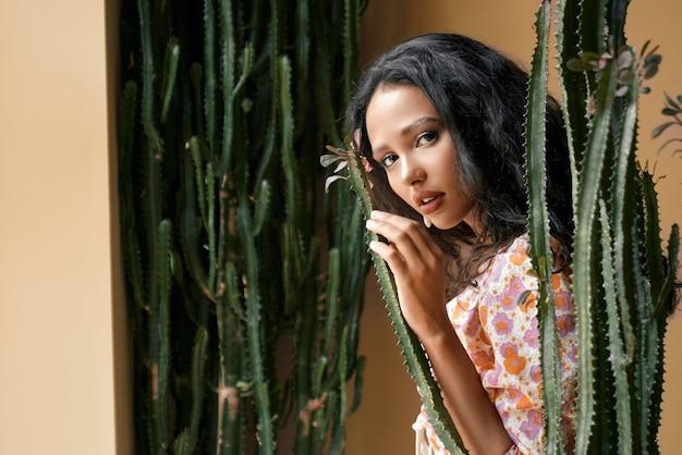 Primo piano di una ragazza sensuale con capelli scuri ondulati tra cactus