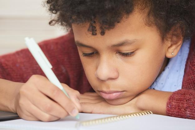 Primo piano del ragazzo africano serio che si concentra sullo studio che si siede allo scrittorio e che fa lavoro di ufficio