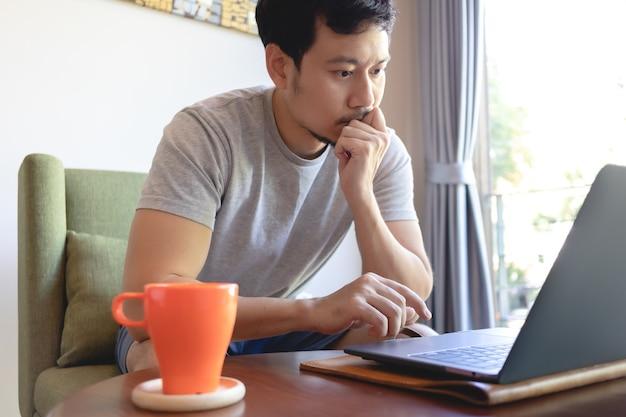 Chiuda in su di un uomo asiatico serio che lavora al suo computer portatile nella caffetteria.