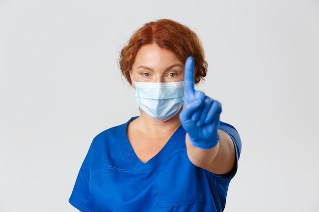 Primo piano della dottoressa seria, infermiera in maschera e guanti che avvertono le persone, agitando il dito in divieto di limitazione.