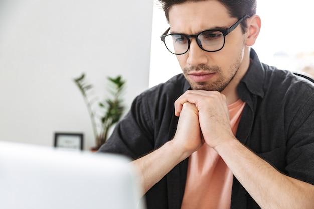 Primo piano serio bell'uomo in occhiali utilizzando il computer portatile mentre è seduto al tavolo in ufficio