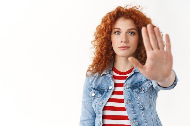 Close-up dall'aspetto serio persuasivo rossa attraente modello femminile domanda stop tenere premuto estendere palmo fotocamera tabù abbastanza gesto dare restrizione divieto cattiva scelta, in piedi muro bianco