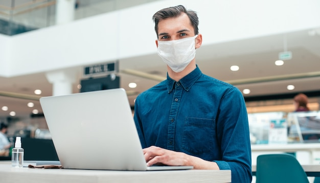 Avvicinamento. uomo serio in una maschera protettiva seduto a una scrivania in ufficio. concetto di tutela della salute
