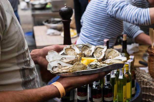 Primo piano del server con vassoio di ostriche fresche sgusciate con spicchi di limone serviti come antipasto
