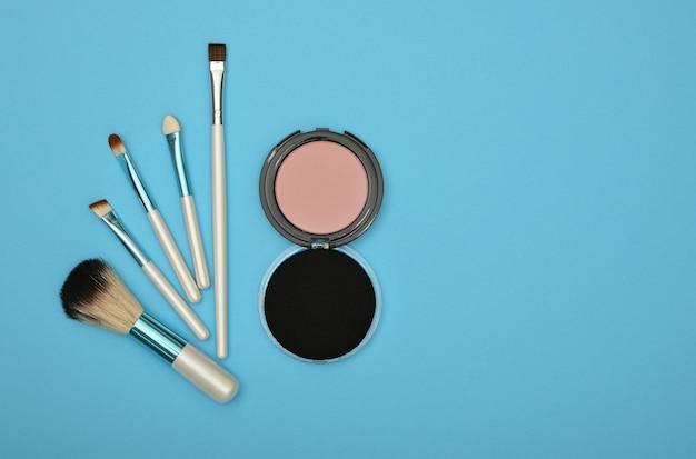 Close up set di trucco viso blush, spugna beige e spazzole su sfondo blu, vista dall'alto in elevazione, direttamente sopra
