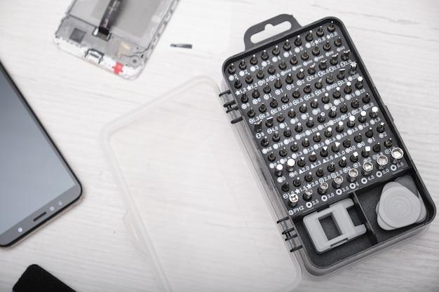 Un primo piano di un set di punte per cacciavite in una scatola nera, guanti, uno smartphone rotto e un set di strumenti per sostituire il vetro del telefono e del tablet