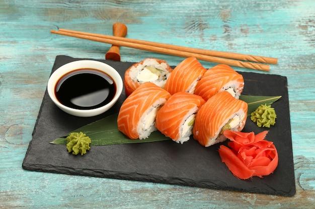 Close up set di sei rotoli di sushi philadelphia con salmone crudo servito sul bordo di ardesia nera sul tavolo blu, ad alto angolo di visione