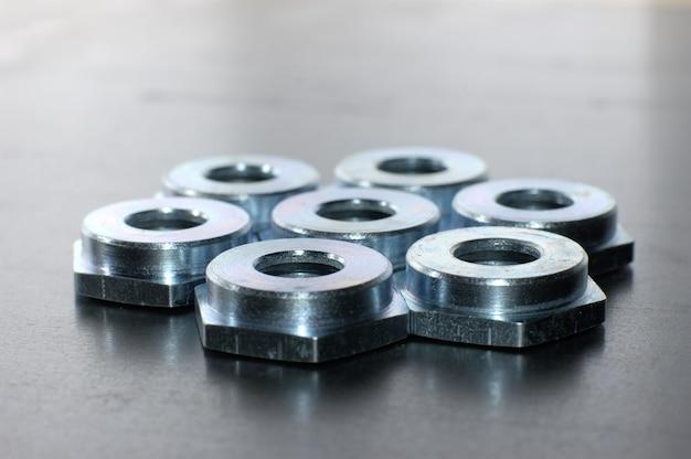 Primo piano di diversi dadi metallici piatti che giace su una superficie metallica in un'officina.