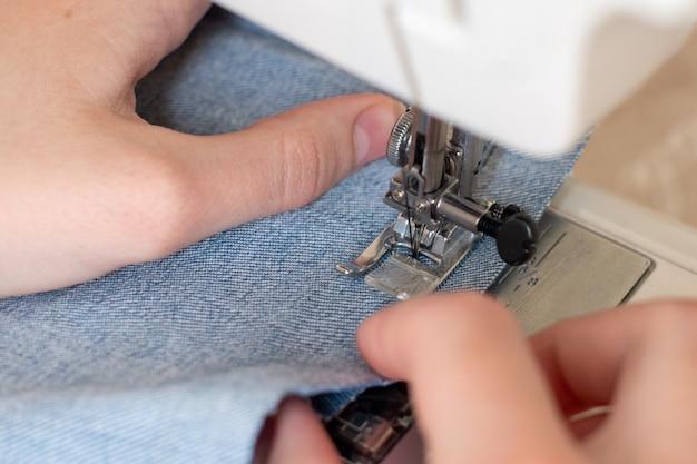 Primo piano della cucitura su una macchina da cucire, le mani guidano il tessuto. il concetto di creatività, hobby.