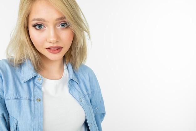 Primo piano di una ragazza bionda sexy con i capelli corti in una camicia blu su sfondo bianco studio.